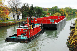 Проходить на барже узкий канал (или реку)